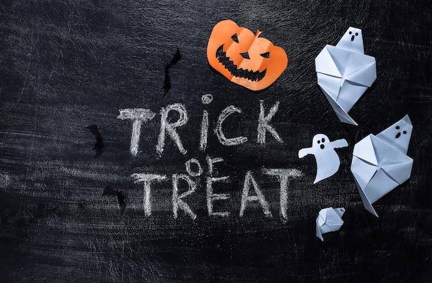 Letras de tiza trick or treat en una pizarra. tema de halloween