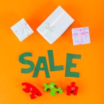 Letras de venta de papel con rompecabezas y cajas de regalo