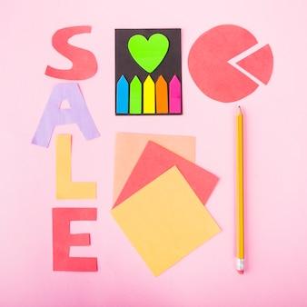 Letras de venta de papel sobre fondo rosa