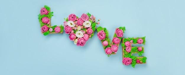 Letras de volumen amor palabra con musgo estabilizado y rosas sobre fondo azul con espacio en blanco para texto. vista superior, endecha plana.