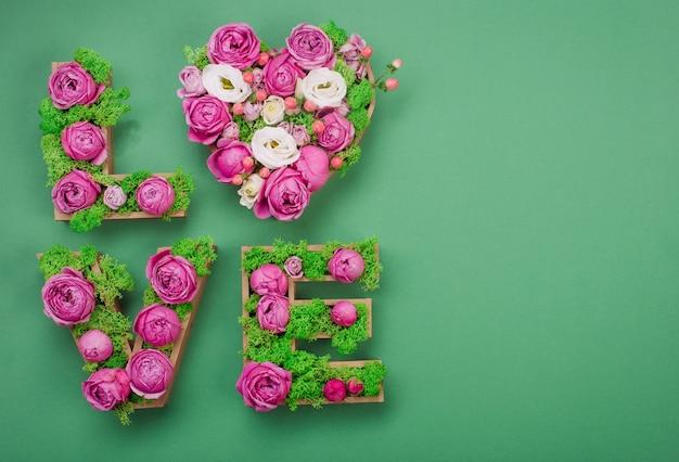 Letras de volumen palabra amor con musgo estabilizado y rosas sobre fondo verde con espacio en blanco para texto. vista superior, endecha plana.