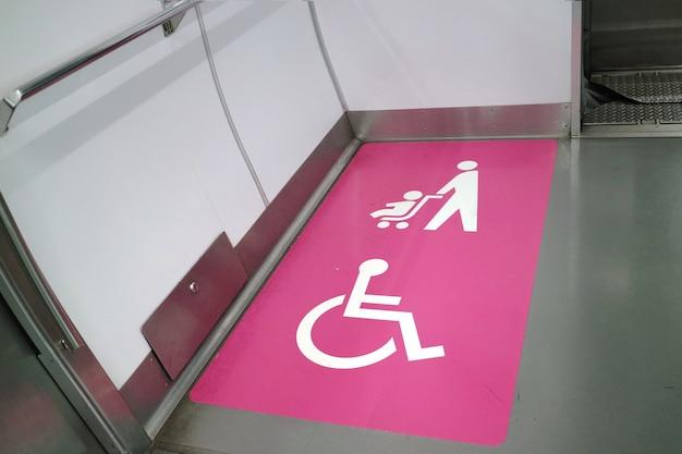 El letrero de área para discapacitados y cochecito de bebé en vías férreas.