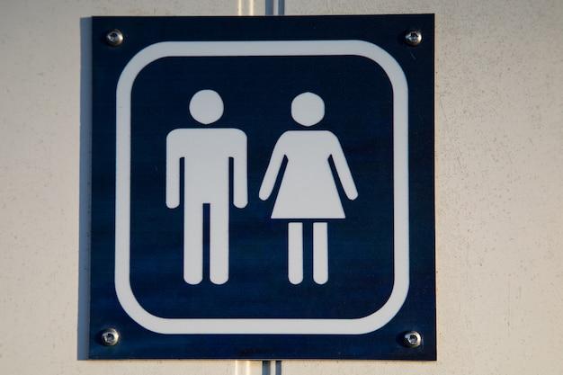 Letrero blanco y azul para inodoro utilizado tanto por hombres como por mujeres.