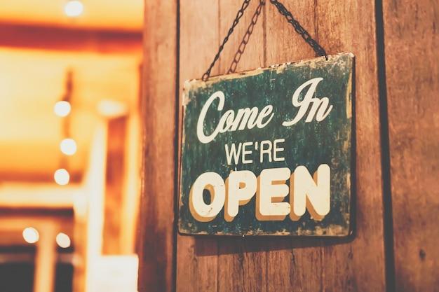 Un letrero comercial que dice abierto en la cafetería o restaurante cuelga en la puerta de entrada.