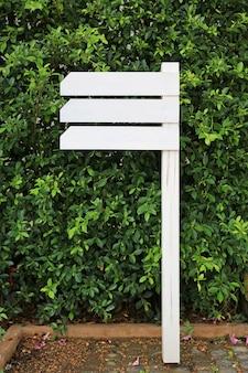 Letrero de madera vacío blanco en el jardín con el área en blanco para el texto.