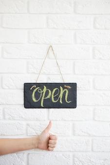 Un letrero que dice abierto en la cafetería o restaurante cuelga en la puerta de entrada. después de la cuarentena la mano muestra el pulgar hacia arriba