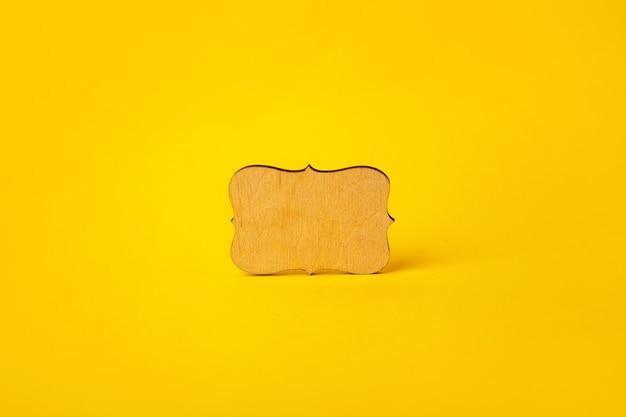 Letrero vacío de madera sobre fondo amarillo, maqueta con lugar para texto