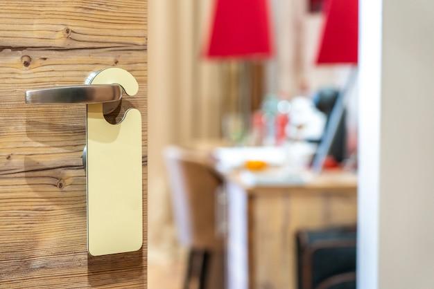 Un letrero vacío en la manija de la puerta del hotel para su texto