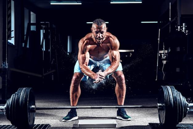 Levantador de pesas musculoso aplaudiendo y preparándose para entrenar en un gimnasio