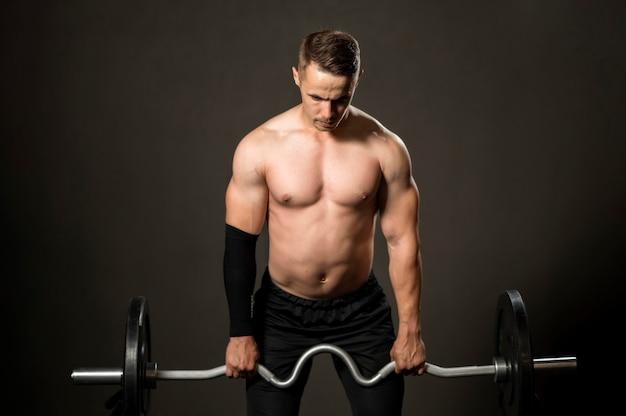 Levantamiento de pesas de hombre de alto ángulo en el gimnasio