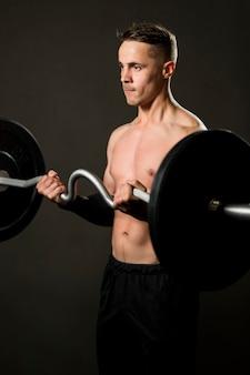 Levantamiento de pesas masculino retrato en el gimnasio