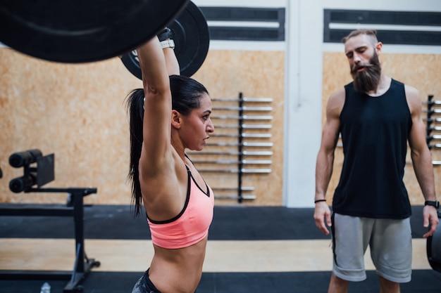 Levantamiento de pesas de mujer joven ayudado por su entrenador personal