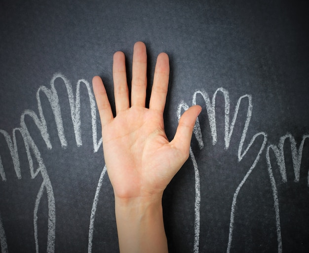 Levantando las manos contra el fondo de la pizarra. mano doodle dibujado en el fondo de la pizarra.