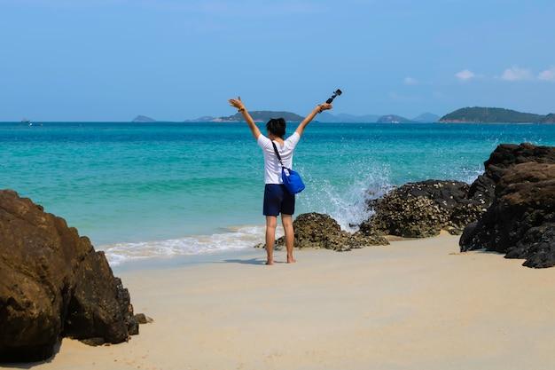 Levántese la vista trasera de la niña con una cámara para relajarse fuera de la playa y observe la vista al mar en la isla de samsan en chonburi, tailandia.