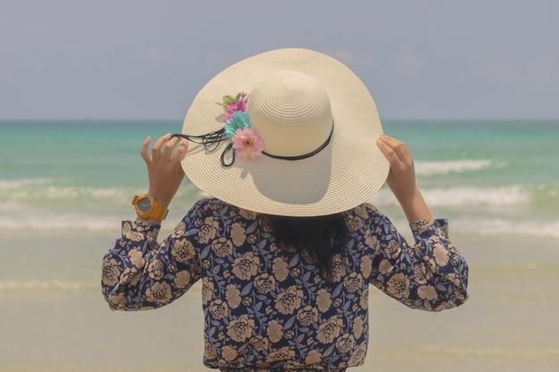 Levántese la vista trasera de la niña que lleva un sombrero para relajarse fuera de la playa y observe la vista del mar en sattaheeb, tailandia.