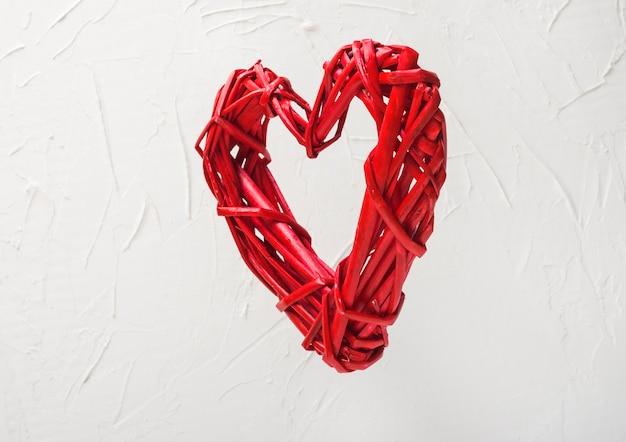 Levitación de un corazón rojo trenzado sobre un fondo blanco concepto de día de san valentín.