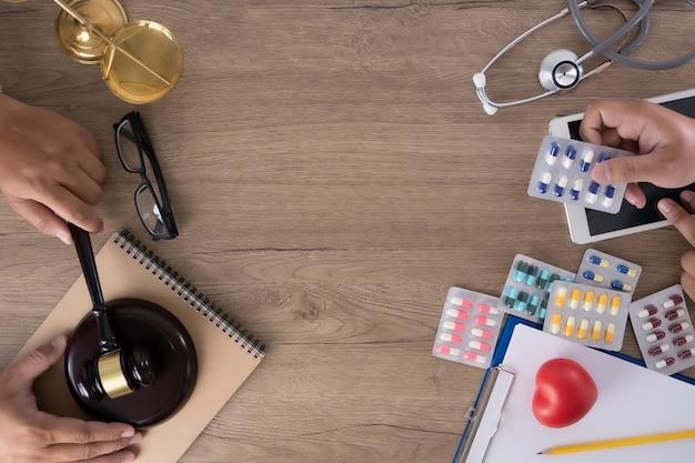 Ley y elementos clínicos en un escritorio mientras las personas usan los objetos.