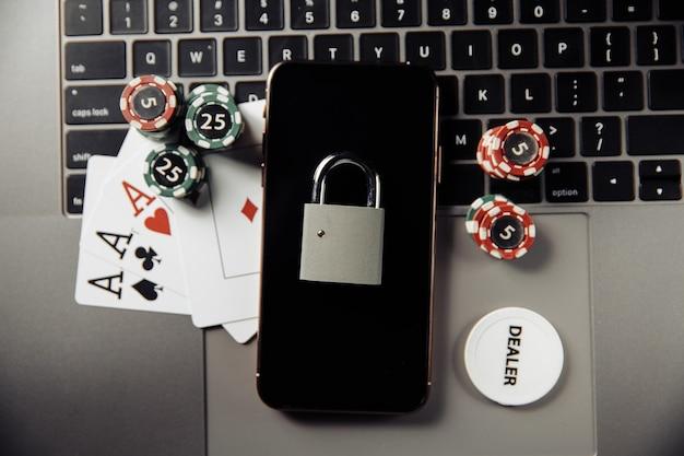 Ley y reglas para el concepto de juego en línea, teléfono inteligente con candado y fichas de juego en el teclado