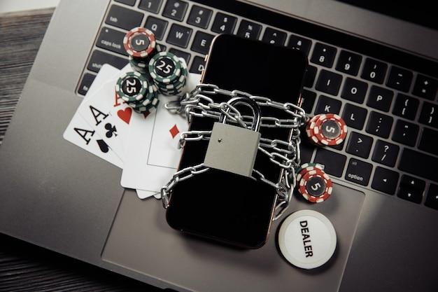 Ley y reglas para el concepto de juego en línea, teléfono inteligente con candado y tarjetas de juego en computadora portátil