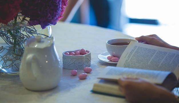 Leyendo un libro con una taza de té y dulces rosados a un lado