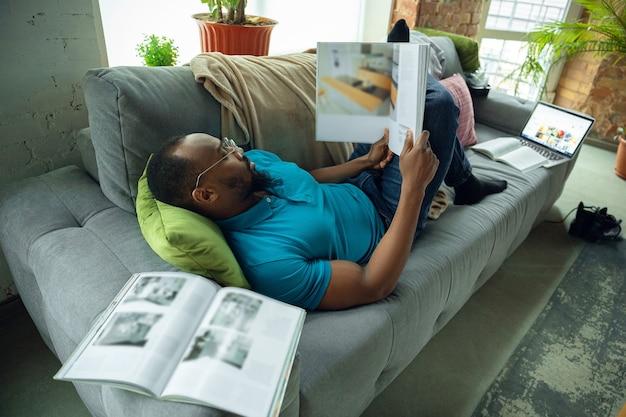 Leyendo libros, revistas. hombre afroamericano que se queda en casa durante la cuarentena debido a la propagación del coronavirus, covid-19. tratando de pasar un tiempo útil y divertido. concepto de salud y medicina.