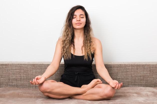 Liberando toda mala energía de las noticias. mujer joven con pelos rizados en postura de loto meditando y haciendo yoga en casa