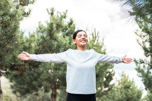 Libertad del alma y del cuerpo. mujer atractiva con los brazos abiertos y los ojos cerrados meditando y entendiendo que está en la naturaleza al amanecer
