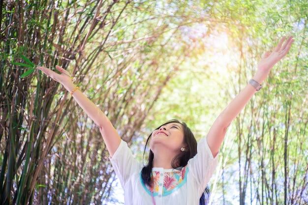 Libertad mujer brazos levantados disfrutando del aire fresco en verdes árboles de bambú.