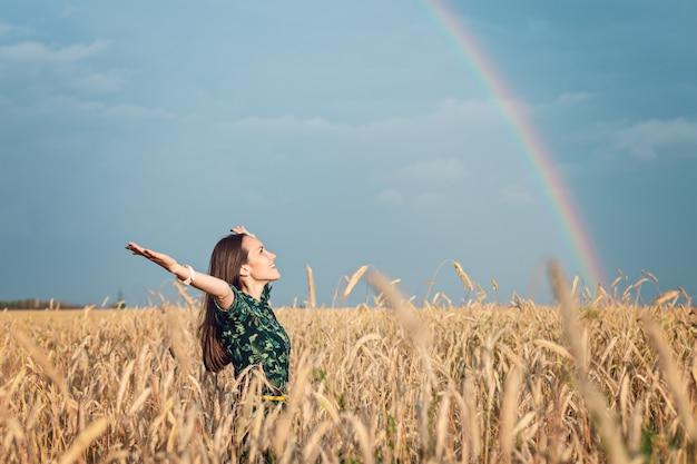 Libertad. mujer con las manos abiertas sonriendo mirando al cielo contra el arco iris