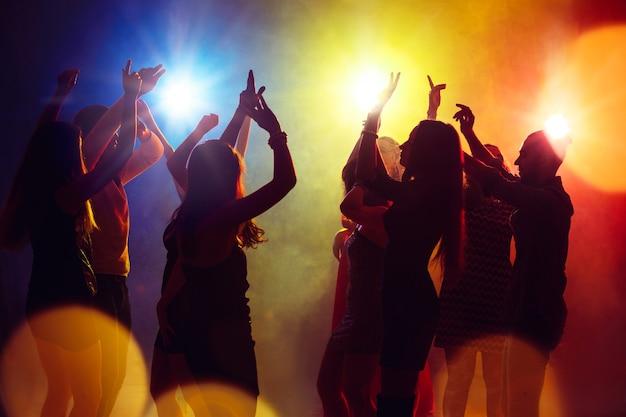 Libertad. una multitud de personas en silueta levanta sus manos en la pista de baile sobre fondo de luz de neón. vida nocturna, club, música, baile, movimiento, juventud. colores amarillo-azul y niñas y niños en movimiento.