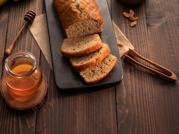 Libra de pan de plátano casero en rodajas con anacardos y miel en la mesa de madera.