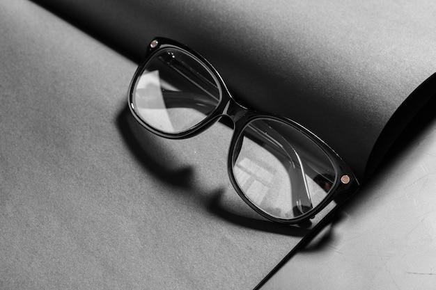 Libreta abierta con gafas de montura negra.