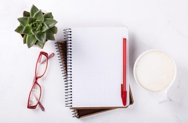 Libreta con bolígrafo, vasos, café y flor.