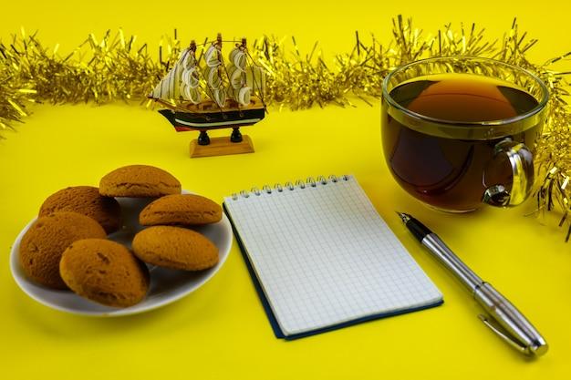Libreta de cuadros con asa, taza de té y adornos navideños amarillos.