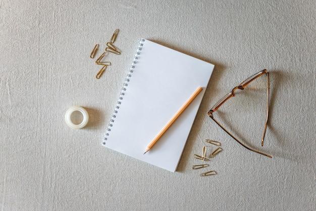 Libreta y lápiz sobre un fondo gris.