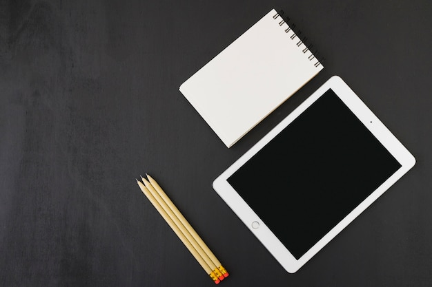 Libreta, tablet y lápices