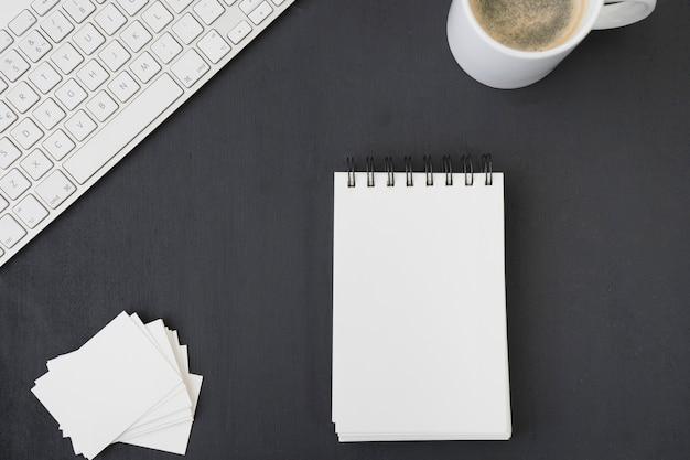 Libreta, tarjetas de visita, café y teclado