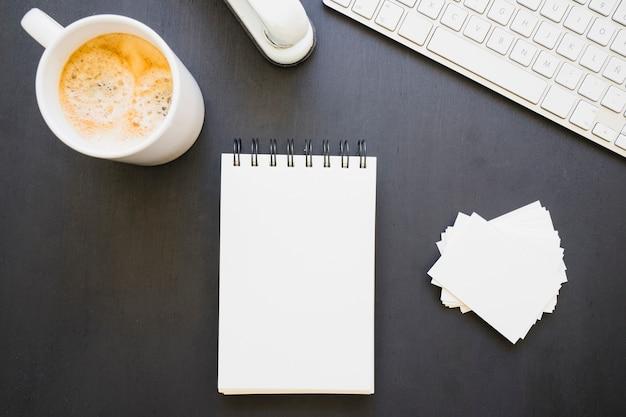 Libreta y tarjetas de visita con taza de café y teclado