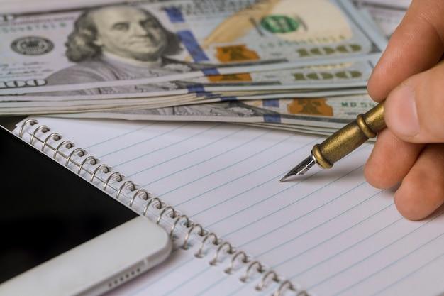 La libreta vacía en la mano del hombre escribe billetes de banco del dólar con la pluma