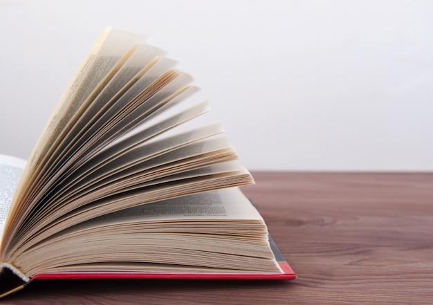 Libro abierto, acostado en una mesa de madera con tonificación.