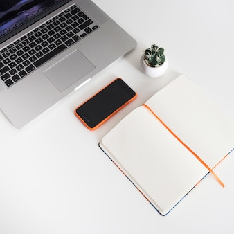 Libro abierto al lado de portátil