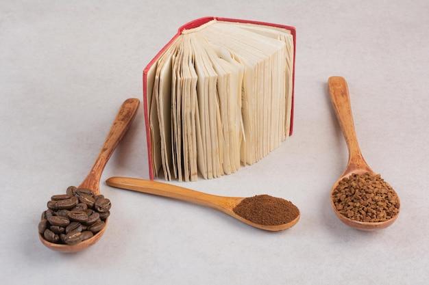 Un libro abierto con cucharas de madera llenas de granos de café y cacao en polvo. foto de alta calidad