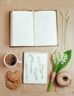 Libro abierto con espacio en blanco para texto cerca de una taza de café y flores de lirios