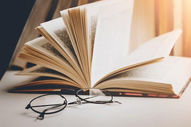 Un libro abierto con gafas sobre una mesa de madera con el trasfondo de un conjunto de libros, tonificación vintage.