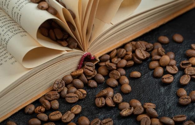 Un libro abierto con granos de café sobre una superficie gris.