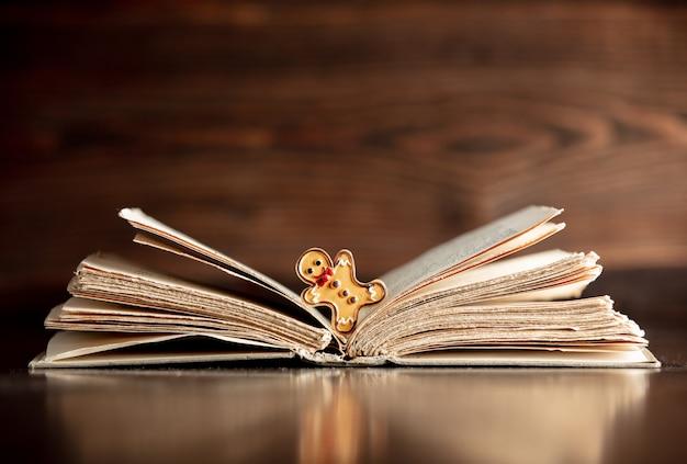 Libro abierto y hombre de jengibre en mesa de madera