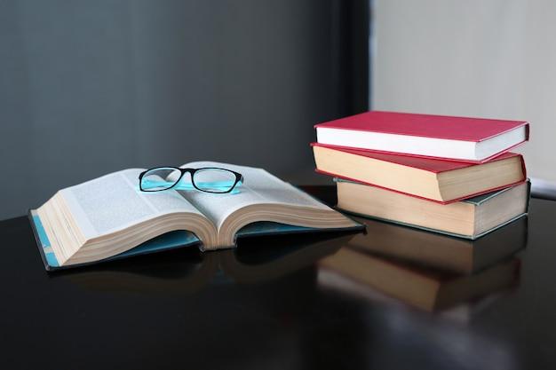 Libro abierto y libros de tapa dura sobre mesa de madera en biblioteca.