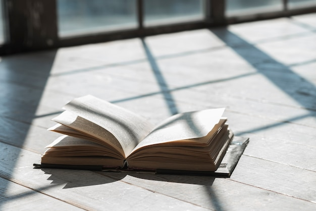 Un libro abierto a la luz del sol en el patio.