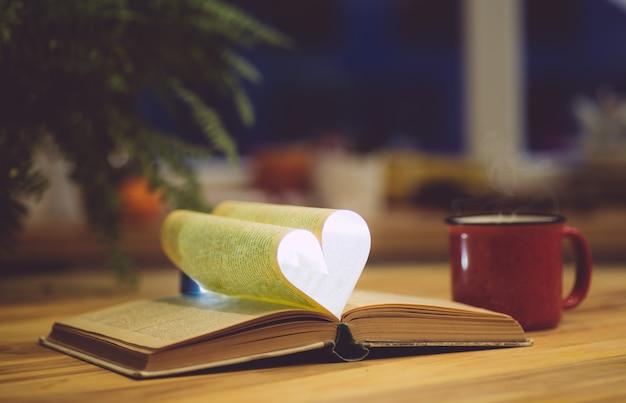 Libro abierto con una página en forma de corazón. conocimiento, educación o concepto de amor.
