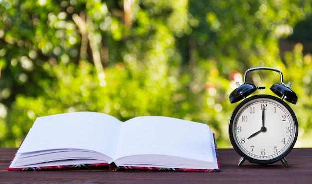 Libro abierto con páginas blancas y relojes.